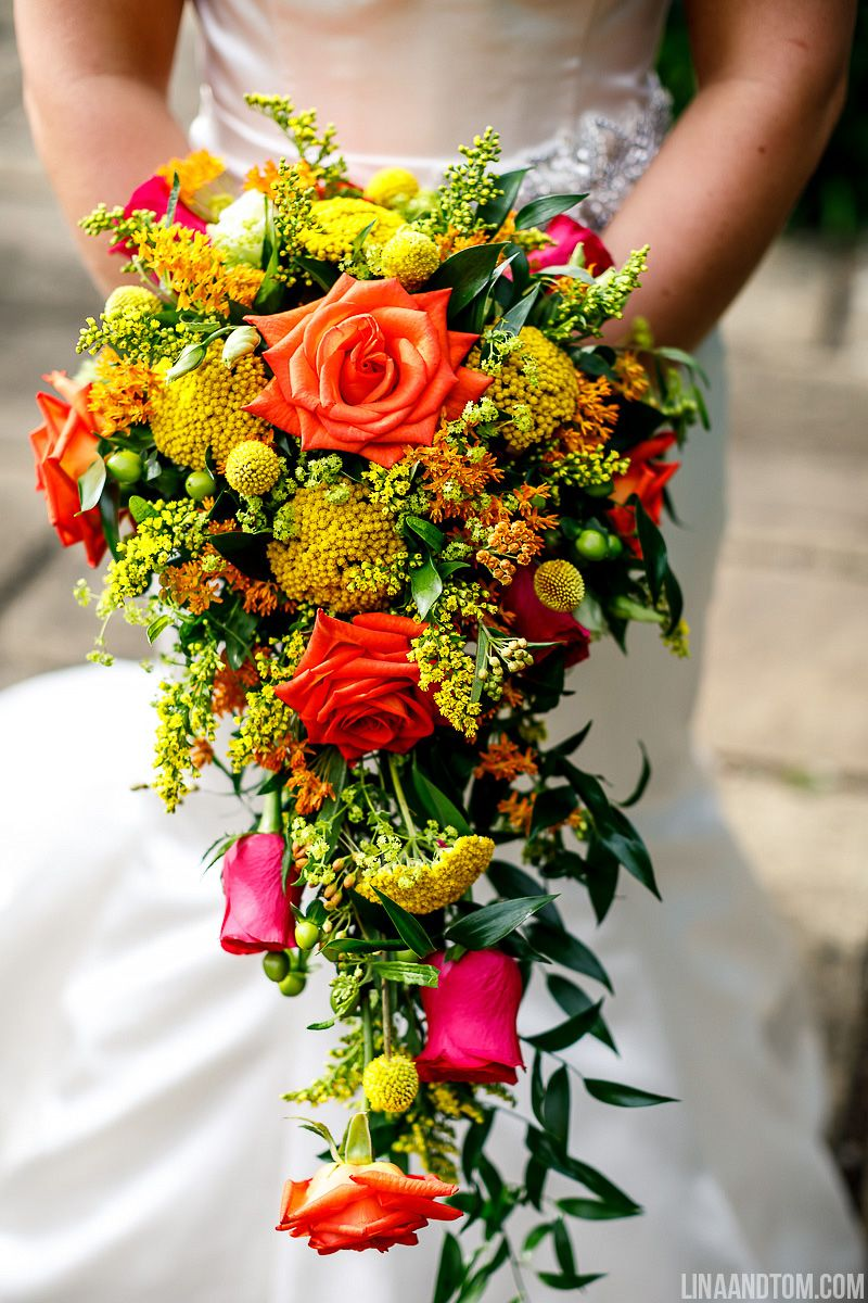 A Cascading Bridal Bouquet Of Orange Pink And Red Roses With