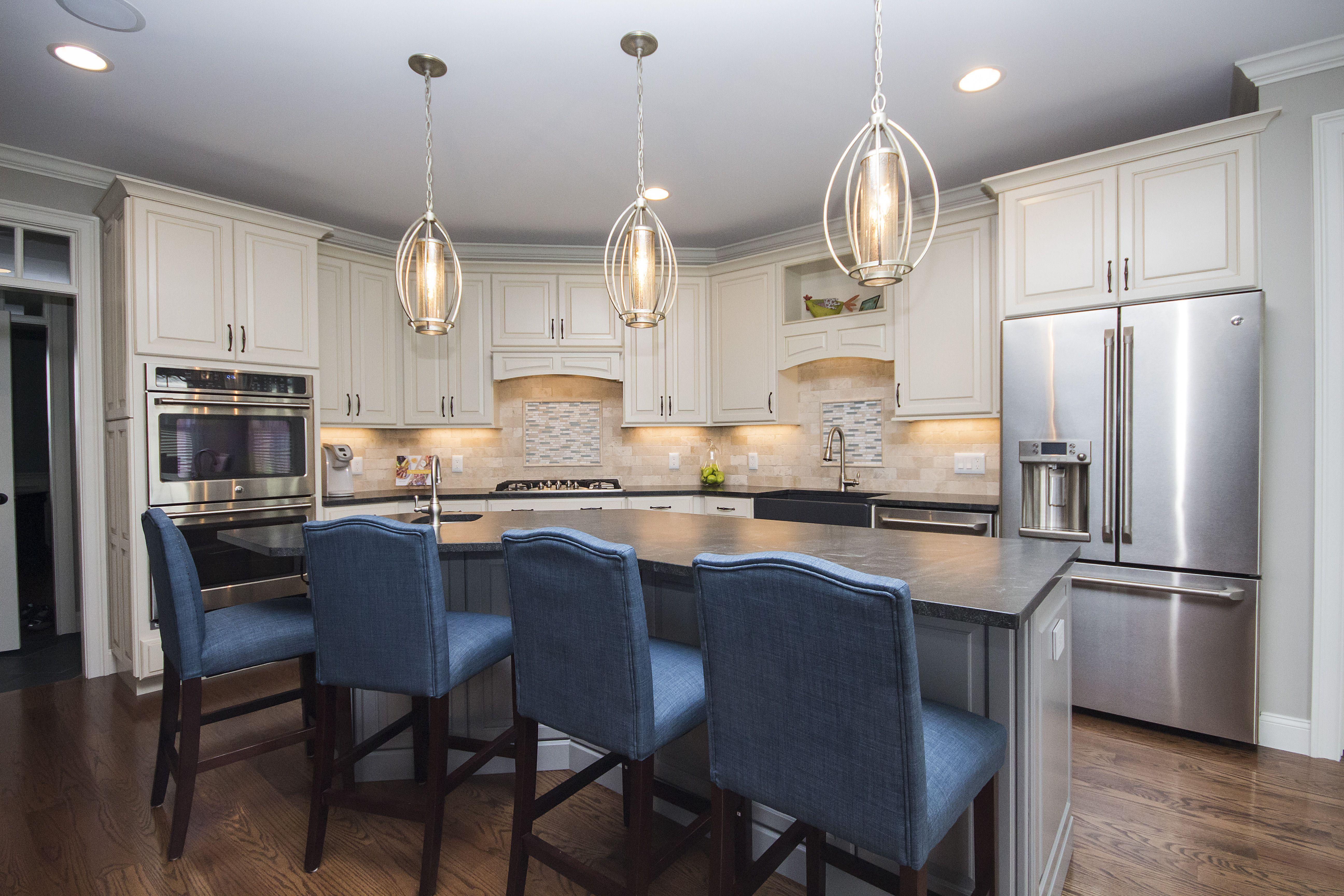 Featuring Cream Cabinetry, Grey Island, Black Granite Countertop, Grey  Farmhouse Sink, Bar Sink, Hanging Jeweled Pendants, Mosaic Blue Glass  Backsplash, ...