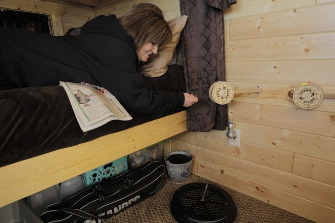 Cathie Kranz on the lower bunk of her queen-sized bunk bed checking a rattle reel—named for the sound it makes when there is a pull on the line—inside her fish house.