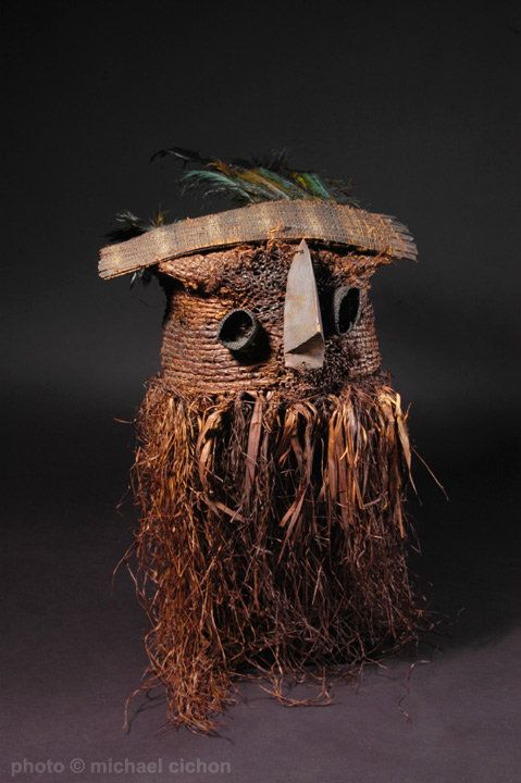 """This type of face mask was worn pulled over the head by young, male initiates of the Binji people, D.R.Congo. made of raffia fiber and chicken feathers, with stitched-on facial features made of light, soft wood; on this mask it is only the nose which is made of wood, the attached eyes are also of fiber. approximately 26""""  Early 20th century. Provenance: Ex-Denver Art Museum-deaccessioned, no. 1988.362 (marked in white). Quite rare."""