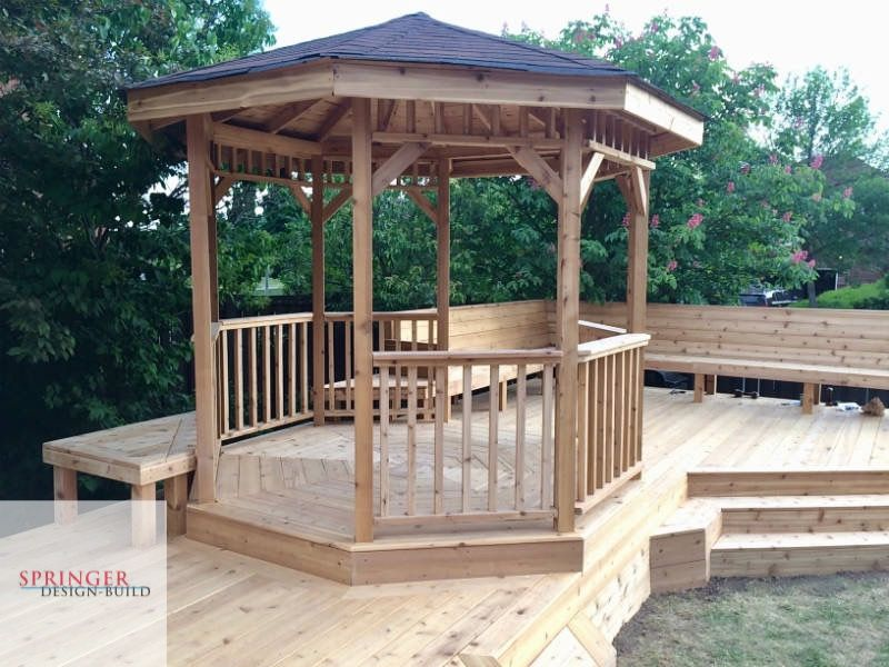 Cedar deck with bench seating, wrap around steps, picture frame border and a gazebo with exposed rafters containing tongue and groove planks and brown ashphalt shingles to top it off.