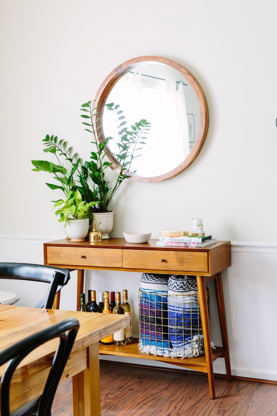 Eclectic Console Table Styled With Wine And Blankets And Plants To Decorate  A Living Room