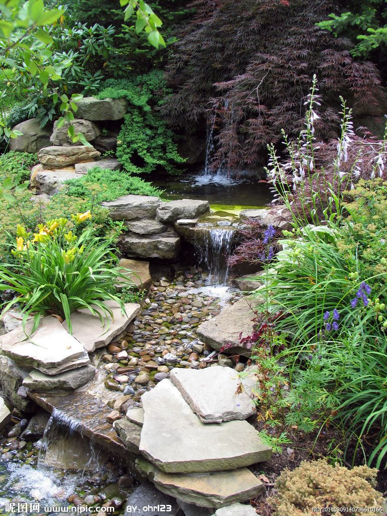 Beautiful water garden interesting how it flows from a for Garden pond waterfall ideas