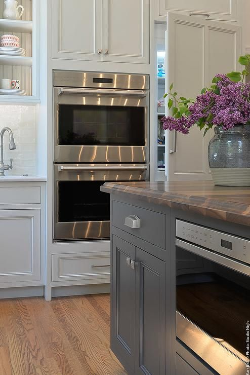 A Pantry Is Concealed Behind A Light Gray Door Positioned Beside A - Light gray shaker cabinets