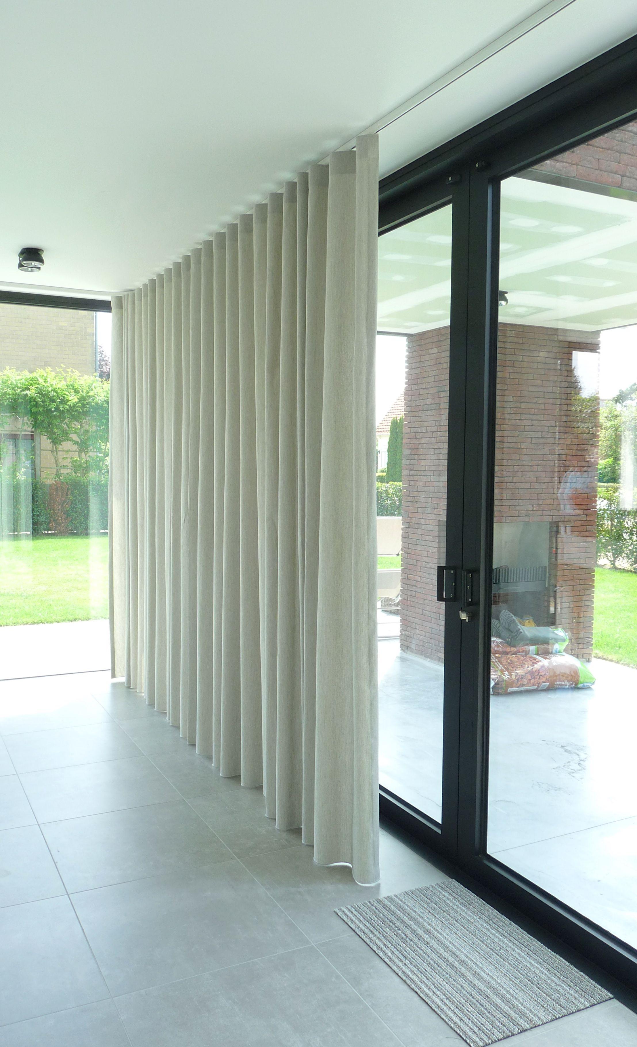 strakke nieuwbouwwoning met grote ramen die zorgen voor veel lichtinval voor de gordijnen werd gekozen voor kamerhoge stof in dezelfde kleur als de