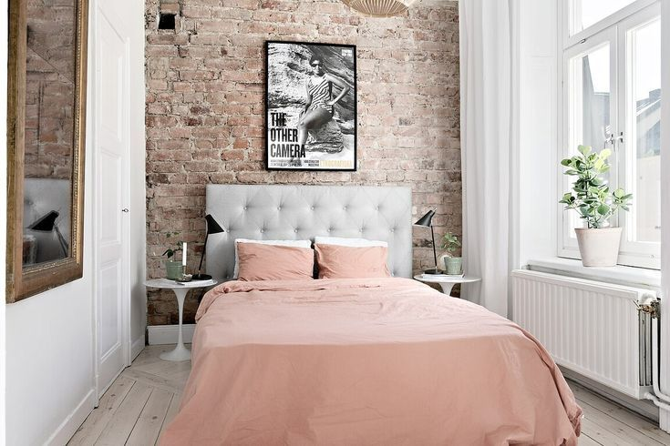 the nordroom  pink bedroom with exposed brick wall
