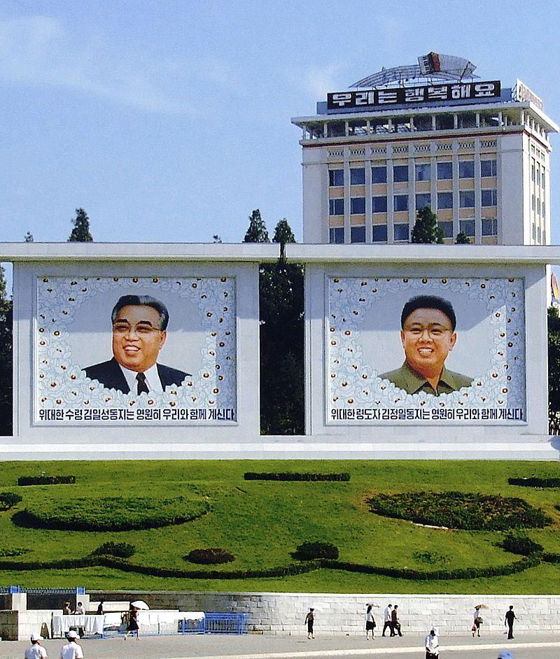Murales de Kim Il-sung y Kim Jong-il en Pionyang. El eslogan del edificio reza: «Somos felices»