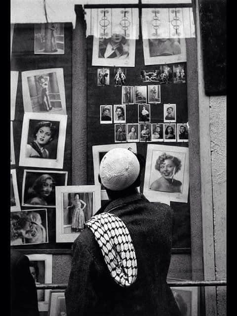رجل ينظر الى الصور المعروضة في احدى استديوهات التصوير في شارع الرشيد عام 1959 ولكن جل اهتمامه هو بطاقات اليانصيب المعروضة في اعلى الص Baghdad Iraq The Old Days