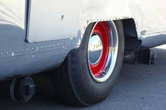 Great example of red vintage trailer wheels, with small baby moon hubcaps and beauty rings