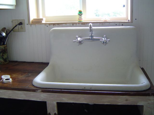 White Old Kitchen Sink Made Of Ceramic Material And Stainless Steel Faucet.