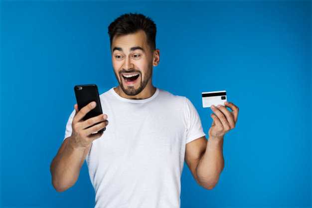Download Surprised Attractive Guy Is Watching On The Cell Phone And Holding Credit Card For Free Attractive Guys Credit Card Credit Card Terminal