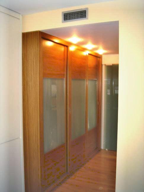 Elegante armario empotrado realizado en madera de teka y vidrio con puertas correderas - Puertas correderas madera y cristal ...
