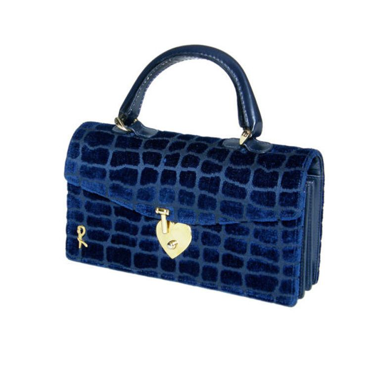 "This classic 1970s Roberta di Camerino handbag features a textured velvet with a reptile skin pattern. The handle, the accordion shaped gussets and the trim are a navy leather. The black leather lined interior has three separate compartments. There is one slip pocket and one zippered pocket inside. The front closes with a heart shaped clasp, and in the corner is a belted ""R"" logo."