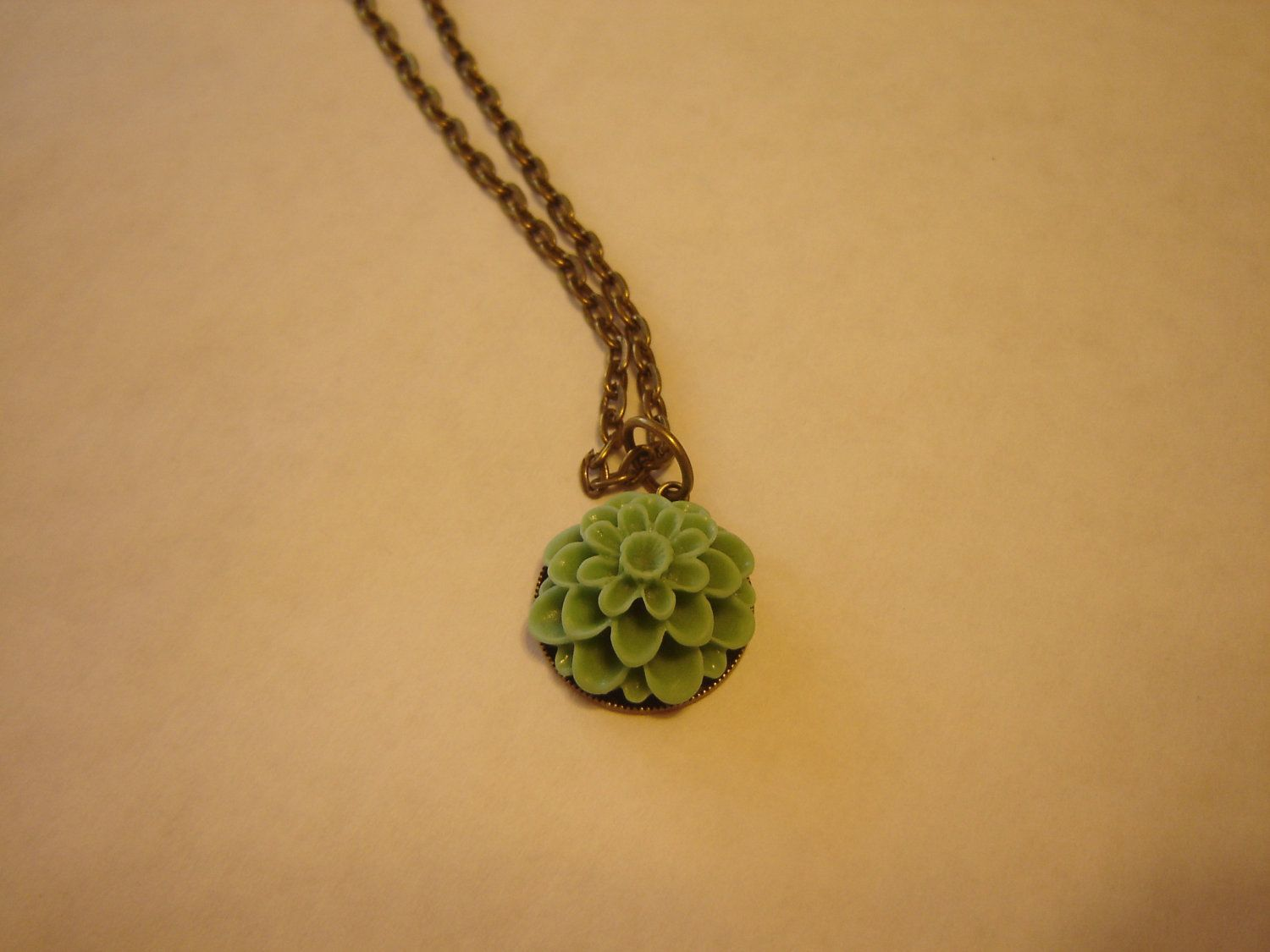 Antique brass necklace with sea foam green chrysanthemum charm, via Etsy.