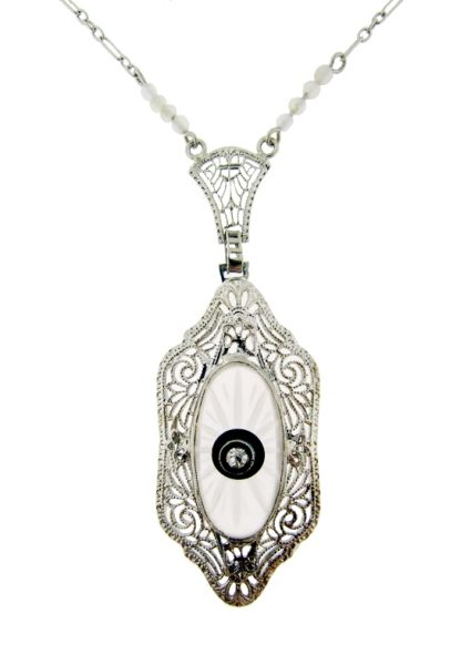 Art Deco Rock Crystal Filigree Pendant. The center features a tiny diamond surrounded by onyx