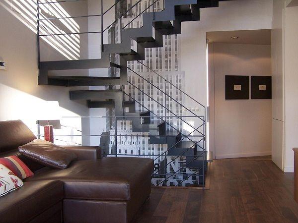 Escalera de estructura metálica con eje central y pasos en madera ...