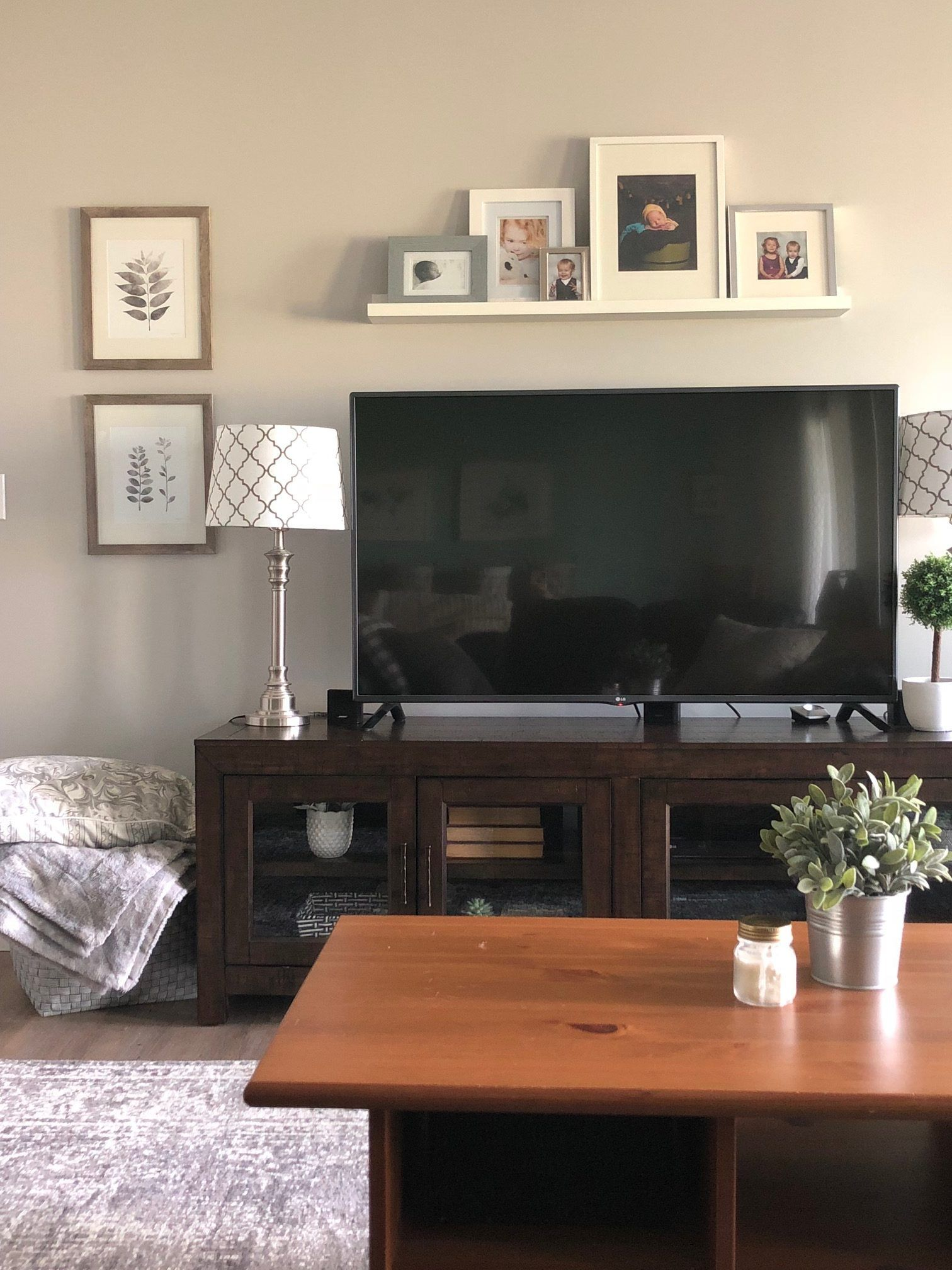 tv console with glass cabinet doors in a basement media