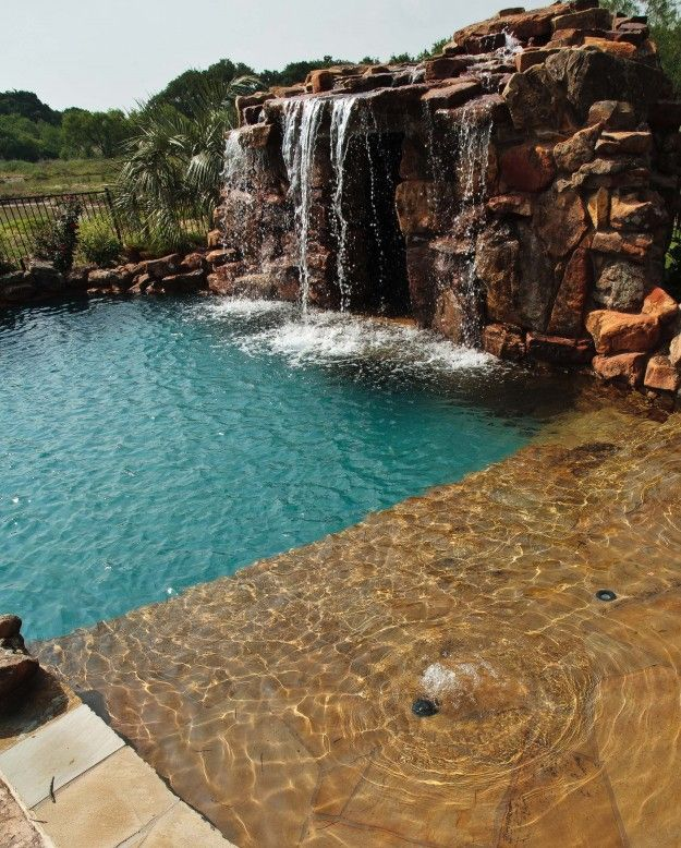 Residential swimming pool with beach entry and waterfall by Water ...