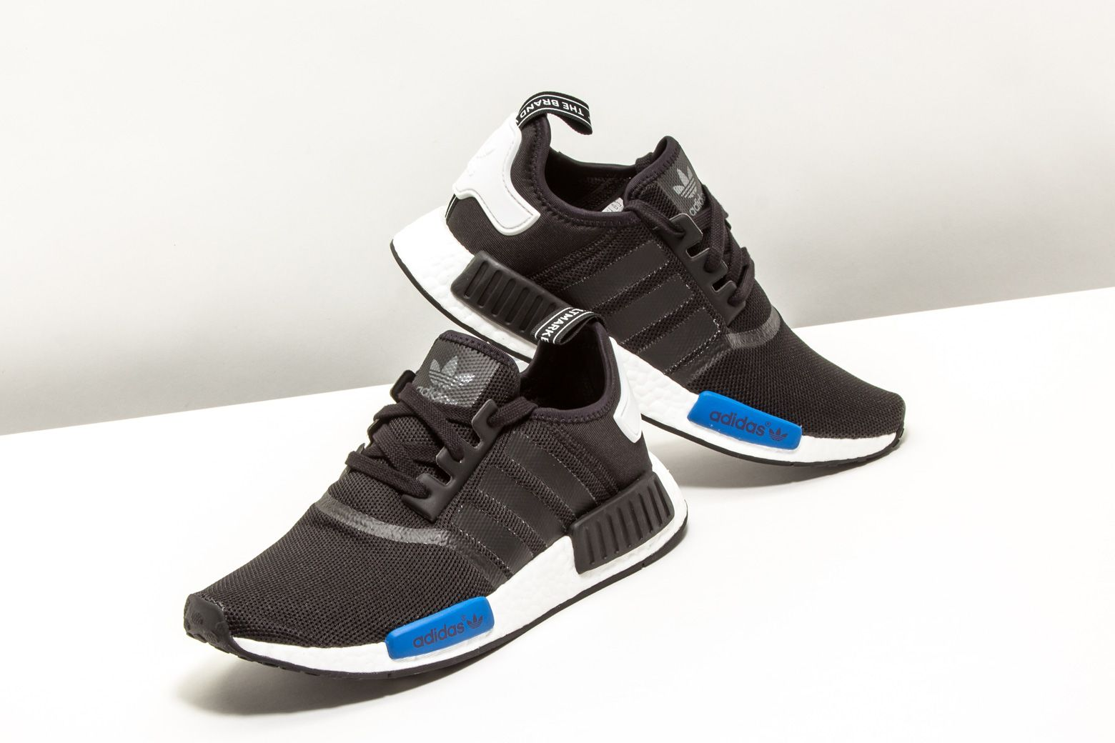 7a5fb8377 adidas outfitted this classic NMD R1 in a Core Black colorway with blue and  white accents.