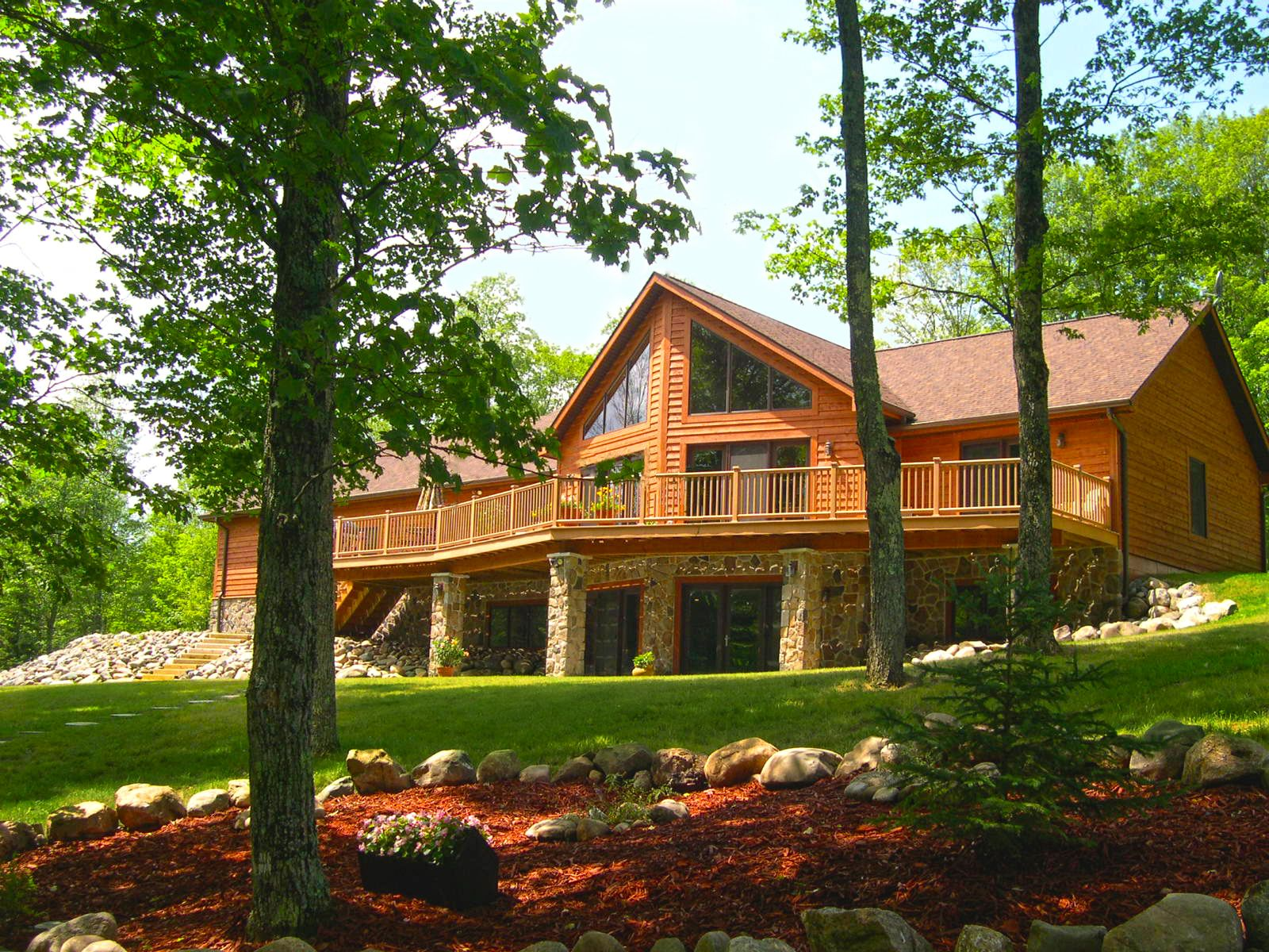 A cedar sided home with a walk out basement with a stone for Rock and cedar homes