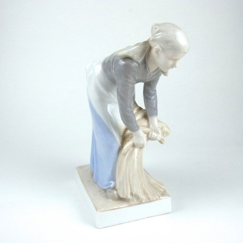 A Royal Copenhagen harvest girl porcelain figure by Christian Thomsen, circa 1905. A Royal Copenhagen harvest girl porcelain figure by Christian Thomsen, circa 1905. Modelled depicting a young woman leaning forward gathering hay, incised with a Christian Thomsen monogram to the top of the rectangular plinth, marked beneath with the green Royal Copenhagen stamp, three wavy lines in blue and numbered 655. 7.4 in (18.8 cm) height.