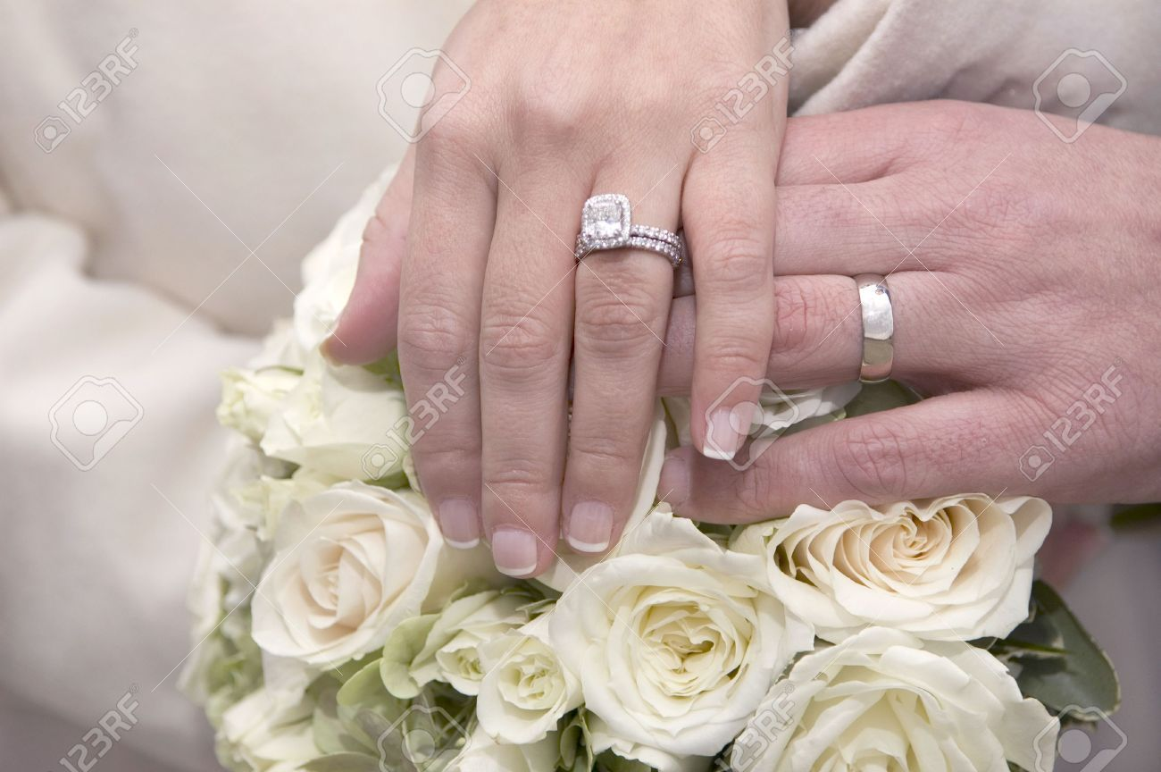 Stock Photo - bride and groom holding hands together, Wedding rings ...
