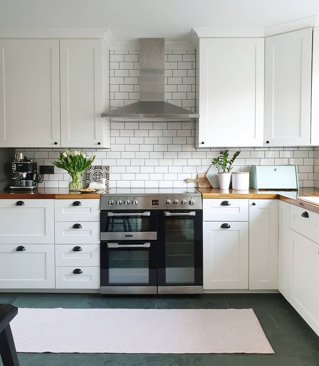 White IKEA kitchen. Black doorknobs and handles. Range