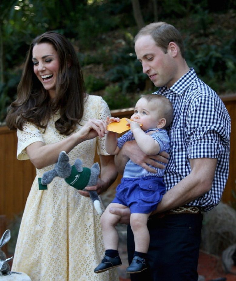 Prince William holds Prince George  as he chews a sticker while Mommy Kate trying to get it out during a 2014 visit to at Taronga Zoo in Sydney, Australia.