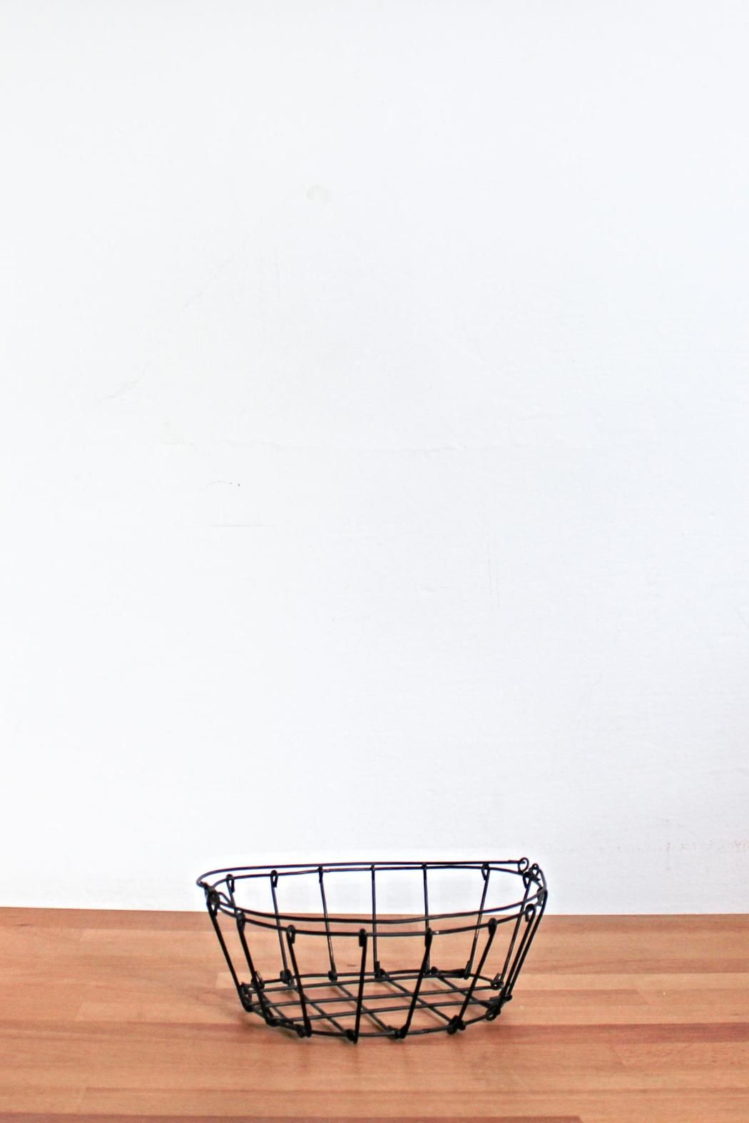 A dozen fresh eggs fit perfectly in this simple wire basket. Perfect for a country kitchen counter with apples or as a bread basket at a family dinner. Iron round table basket with handle.    Dimensions:D 21cm x H 7cm   Oval Wire Basket by Fog Linen Work. Home & Gifts - Home Decor Canada