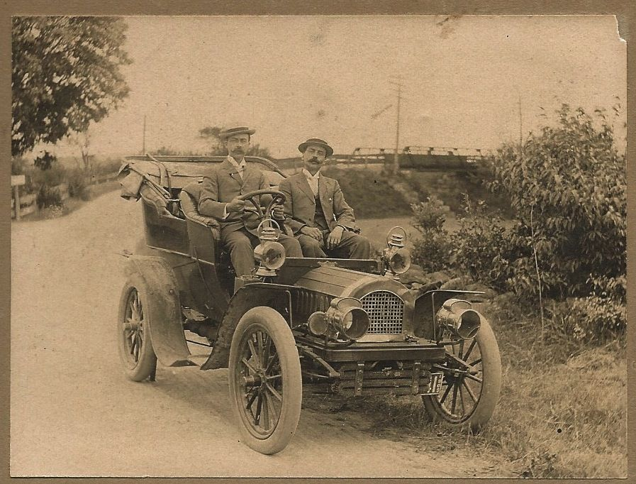 Found photograph of two men in a 1909 automobile.