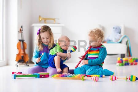 music: Children with music instruments. Musical education for kids. Colorful wooden art toys. Little girl and boy play music. Kid with xylophone, guitar, flute, violin. Early development for toddler and baby Stock Photo