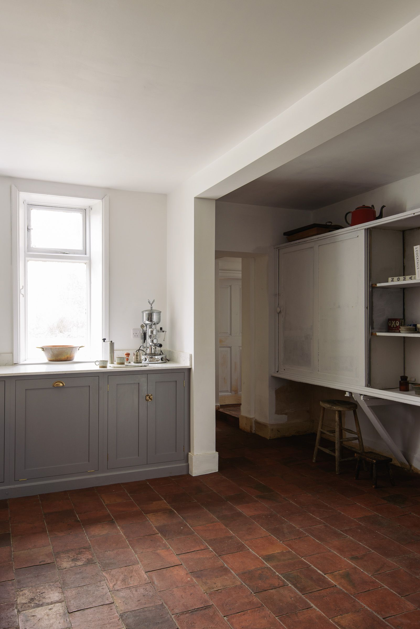 white walls, grey cupboards and deep quarry tiles in deVOL