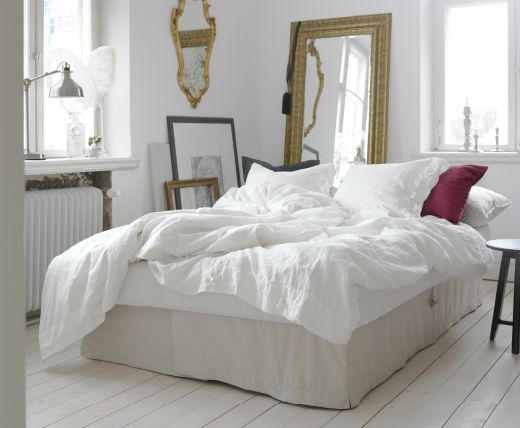 A light living room with a beige sofa-bed converted into a bed for ...