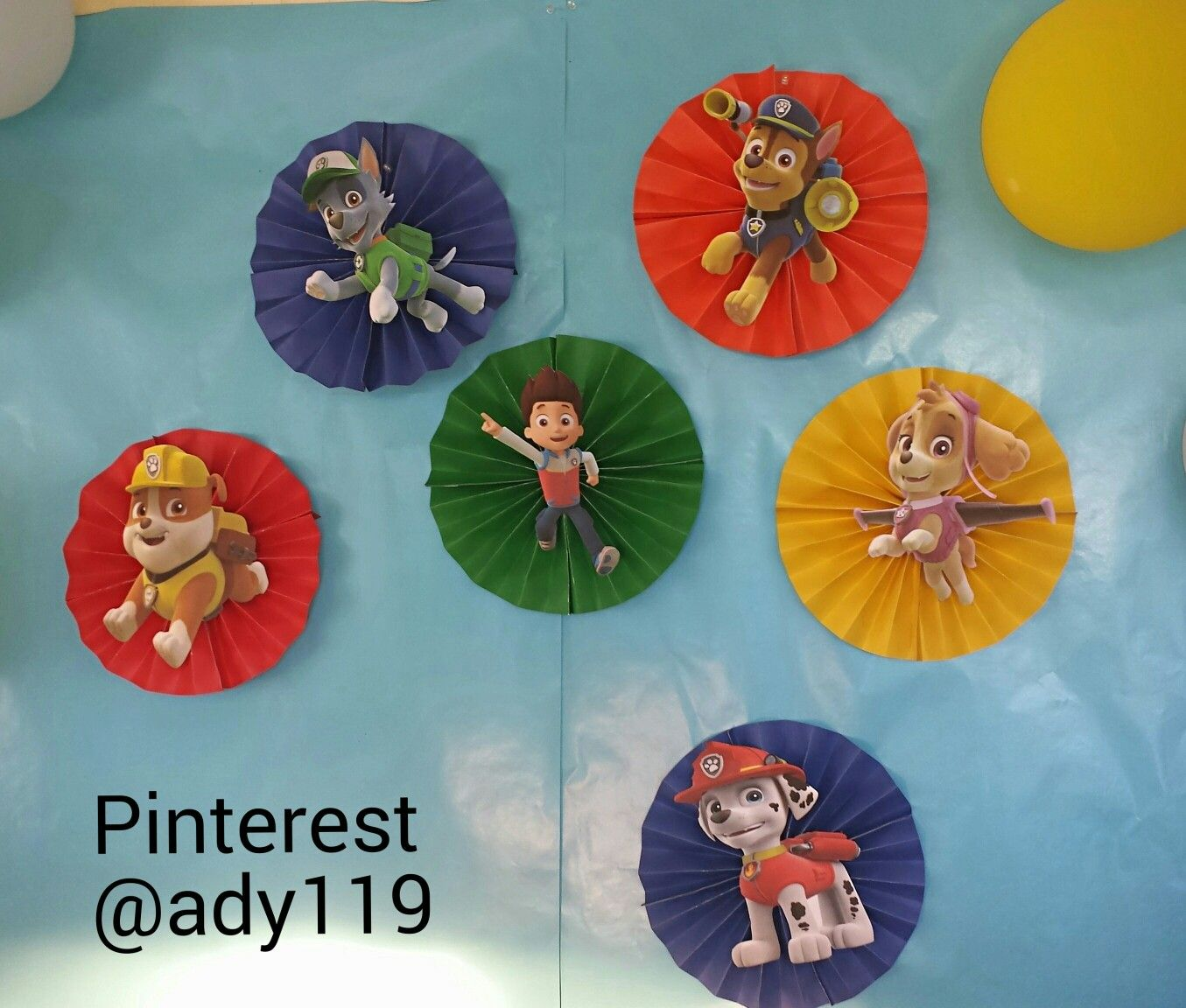 Paw Patrol backdrop. Crafting cover paper fans with character printouts on card stock. 2 images per sheet of paper. Blue background is gift wrapping paper.