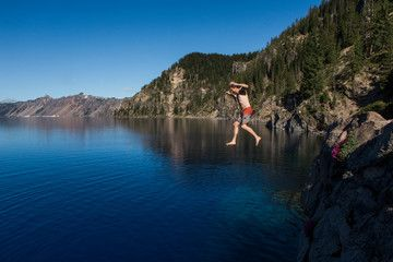 A young man jumps into the cold clear waters of Crater Lake