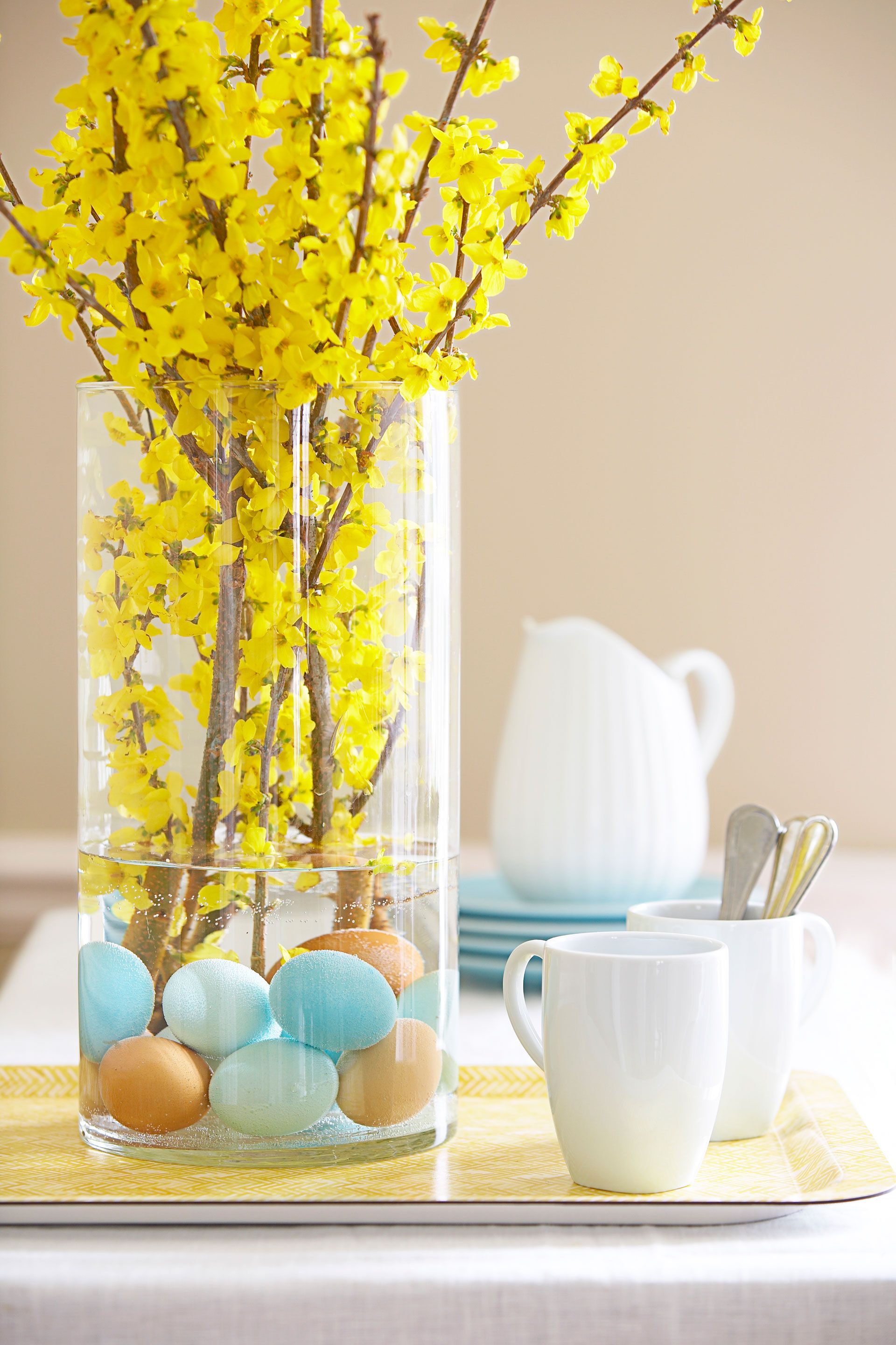 Anchor brilliant forsythia — and give a tongue-in-cheek nod to Easter — with subtly hued hard-cooked eggs. Carefully place a dozen brown, white, and dyed ones (rinse them well first) into a vase, add water, and insert branches.