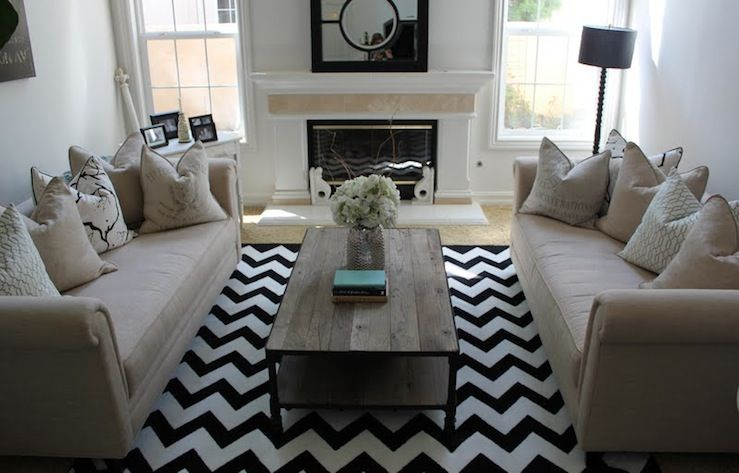 Beautiful living room design with white & black zigzag chevron rug, industrial cocktail table, camel rolled arm sofas, pillows, fireplace, spool floor lamp and mirror.