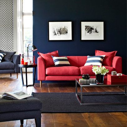 Rich blue walls and red sofa with dark wood floors for Navy couch living room