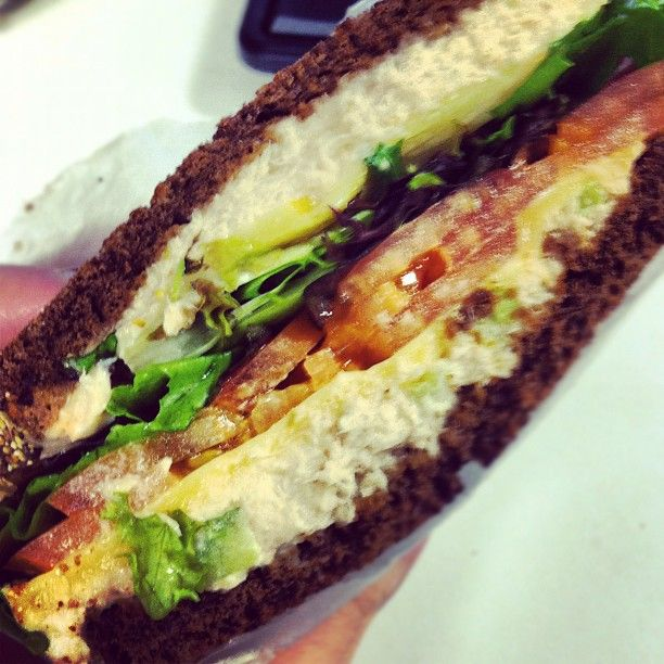 Tuna salad with lettuce, tomato, and melted Gouda on pumpernickel toast