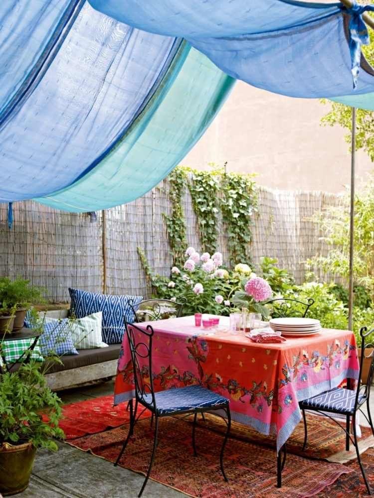 décoration terrasse de style bohème avec auvent en tissu ble et tapis à  motifs