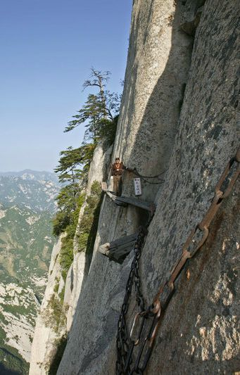 """The trek at Mt Huashan, China has been made famous by the perilous """"plank road"""" involving a series of narrow wooden planks and metal rungs bolted into the side of the mountain."""