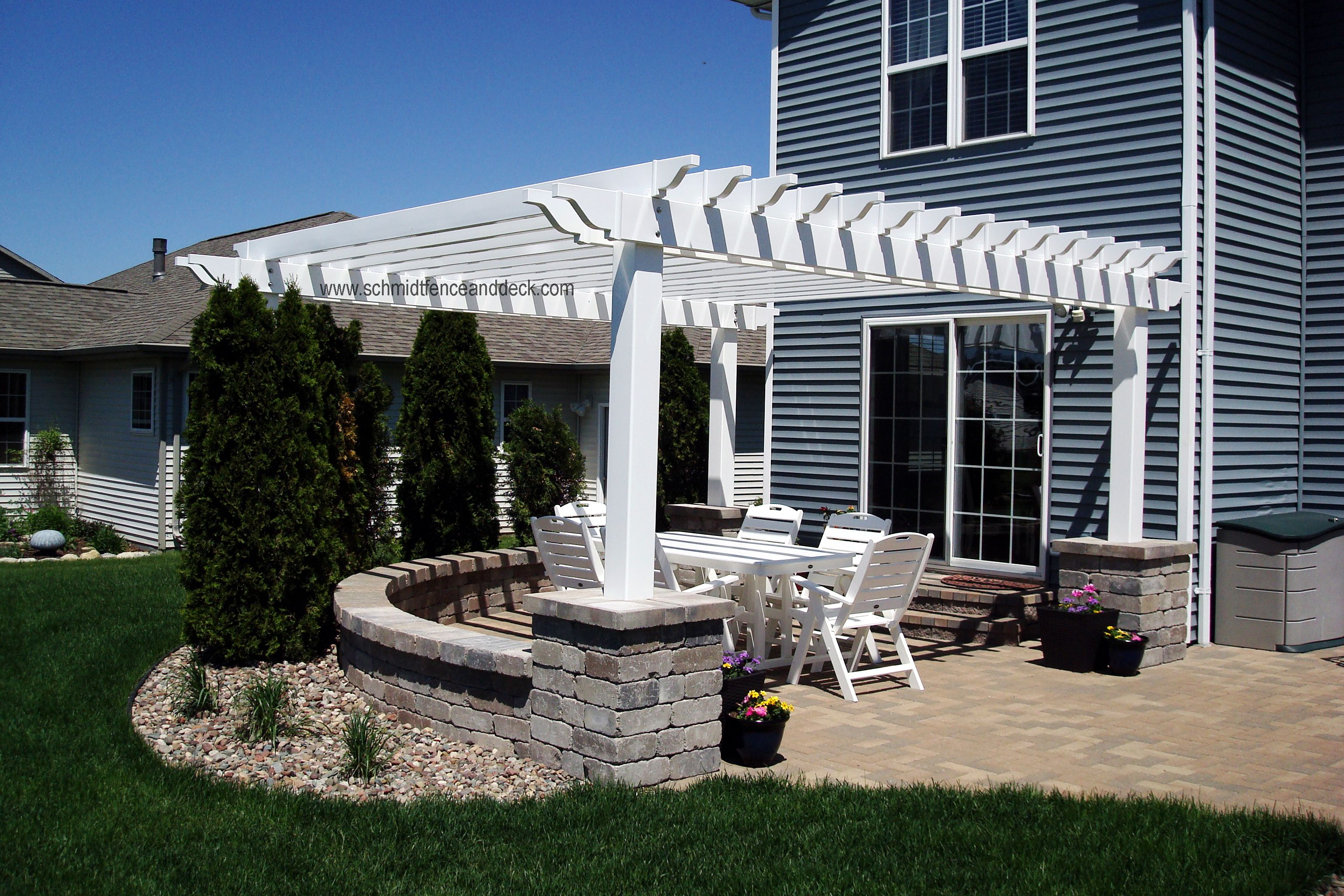 White Vinyl Pergola Over Brick Patio, With Concrete Columns And Seat Wall.