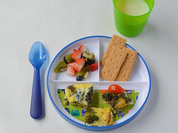 Three-sectioned plate filled with frittata, wholegrain crackers and strawberries and kiwi.