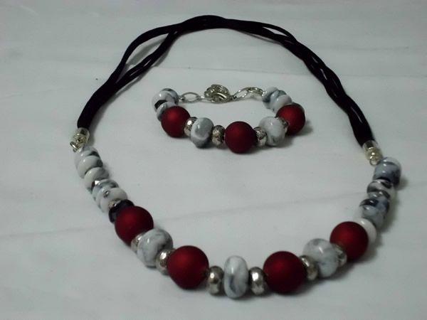 Collar y pulsera ajustable. Cordón cola de ratón negro, discos acrílicos con aguas grises, cristal checo facetado negro, separadores tipo donut de plata tibetana y perlas Polaris rojo magma.