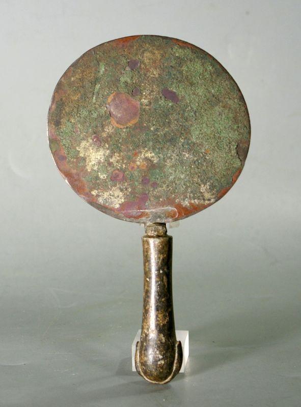 miroir égyptien circulaire, à manche cylindrique en pierre noire, terminé par deux têtes de cygnes stylisées.  (Manche rapporté) Bronze et pierre Egypte Nouvel Empire  Ht.19.5 cm