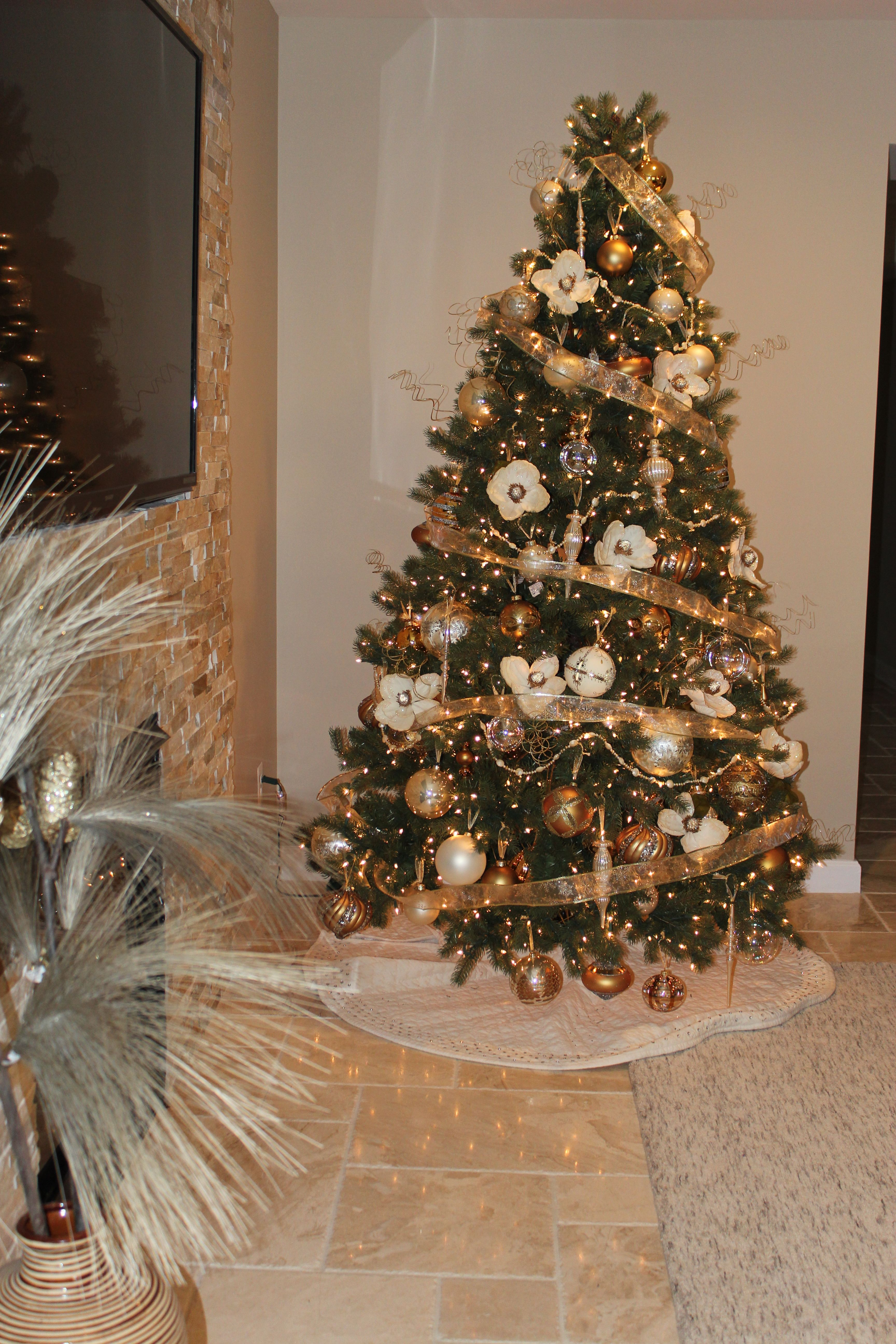 Gold Ribbon Ornaments And Magnolia Flowers Make Up This Beautiful Christmas Tree Christmas Tree Beautiful Christmas Trees Classic Christmas Tree