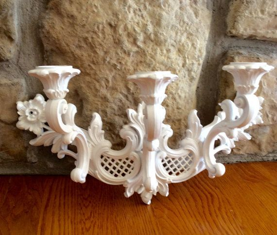 This is a beautiful vintage white three arm sconce candleholder. Ornate curved French/Italian design. Made of a sturdy plastic composite material ( Syroco/Homco). Place glass votives in holders for a stunning wall candle light. ( several glass votives sold in shop). In good vintage condition! Hooks on back ready to hang. Great for bedroom, bathroom, or statement wall decor. I have one in original gold for sale in shop!  Measures 16 wide x 8.5 height x 7.25 wall depth  Thanks for shopping…