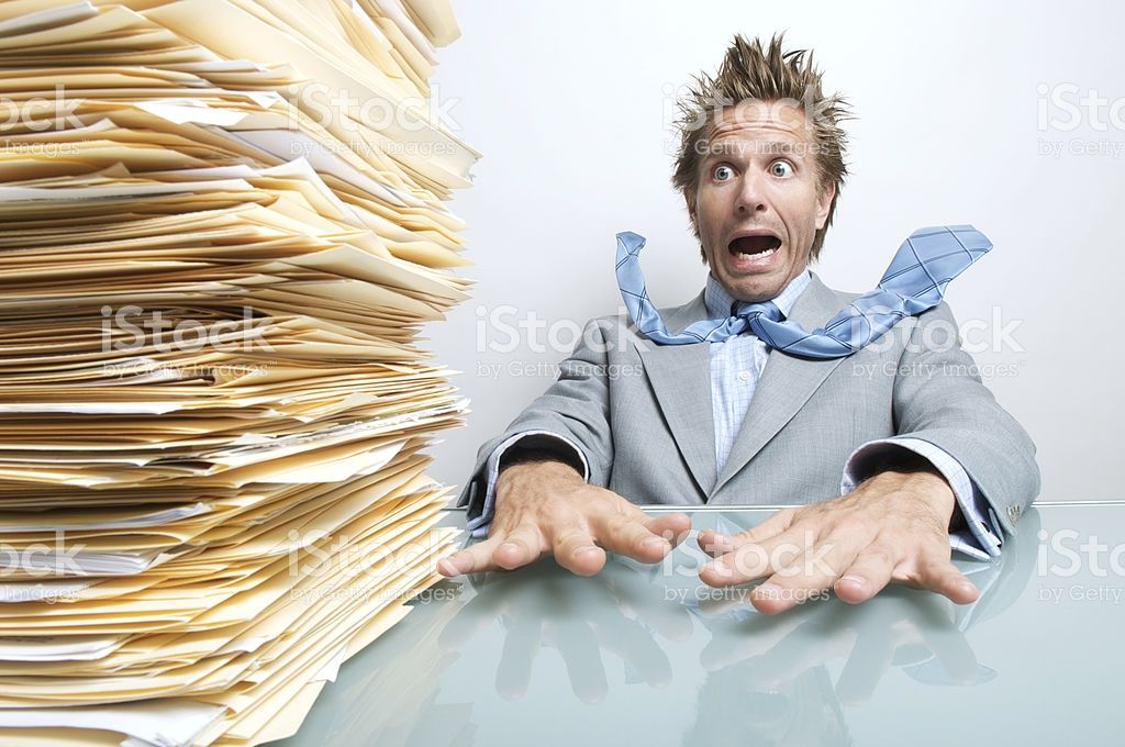 Office worker gasps at the huge stack of paperwork on his