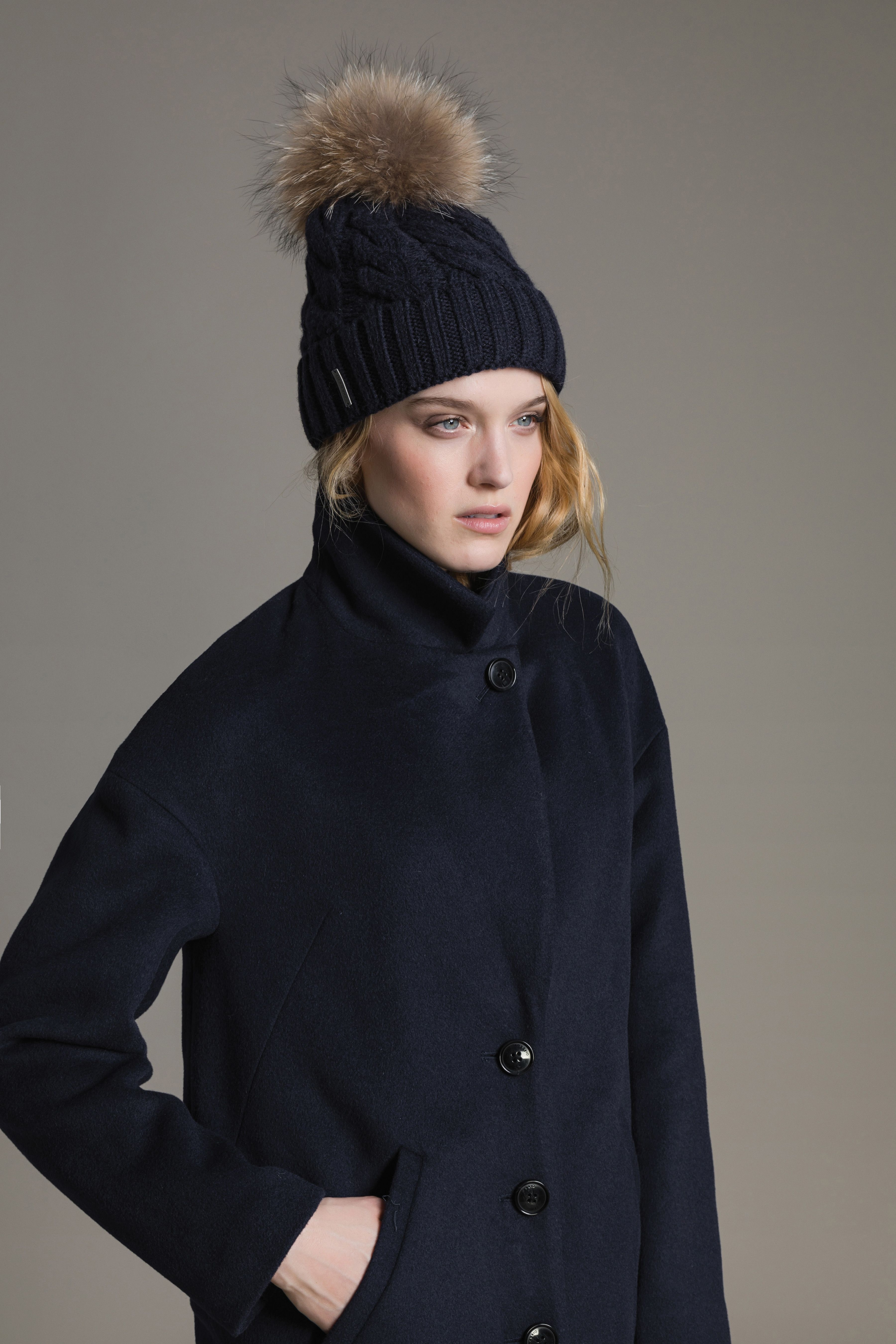 4addc393c56 AMALIE by SOIA   KYO is a cable knit hat with a removable natural fur pom  pom. Its classic folded rib knit hem frames the face and keeps your ears  toasty ...