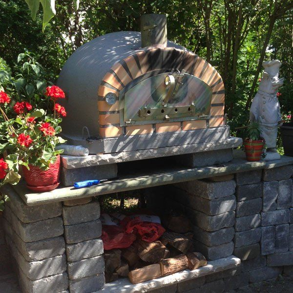 This Pizzaioli Brick Wood Fired Oven is painted grey and a wonderful addition to a beautiful outdoor kitchen.  – Patio & Pizza